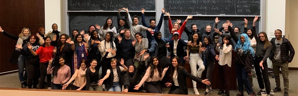 A group of students voguing in front of a blackboard